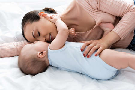 mother with closed eyes lying on bed with baby boy