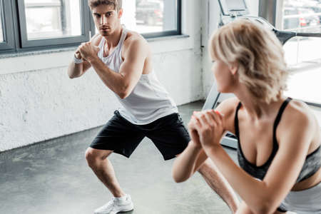 selective focus of young sport couple with clenched hands looking at each other and exercising in gym