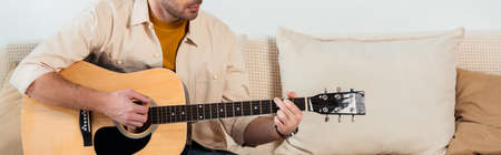 Panoramic crop of young man playing acoustic guitar in living room 免版税图像