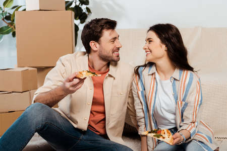 Couple smiling at each other while holding pieces of pizza near cardboard boxes in living room