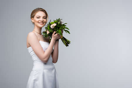 positive bride in white dress holding wedding flowers isolated on grey
