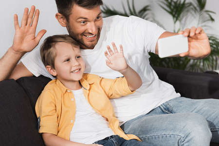 happy father and son waving hands dring video chat on smartphone