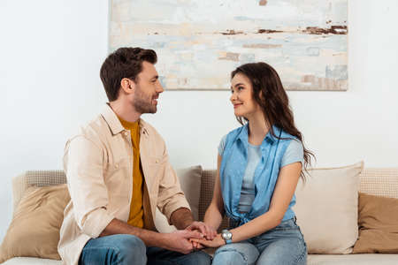 Smiling couple looking at each other and holding hands on sofa at home