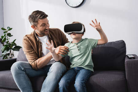 smiling father touching surprised son using vr headset and gesturing whiles sitting on sofa 免版税图像