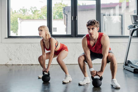 sport couple exercising with heavy dumbbells in gym