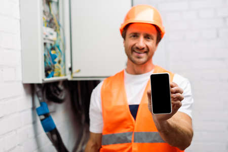 Selective focus of smiling electrician holding smartphone with blank screen near electrical distribution box