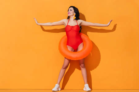 happy girl in swimsuit with inflatable ring and outstretched hands standing on orange Stok Fotoğraf