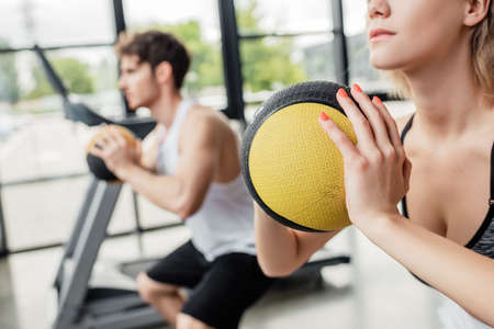 selective focus of young sportswoman exercising with ball near sportive man