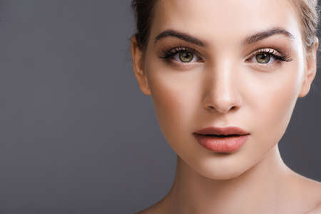 beautiful young woman with makeup looking at camera isolated on grey