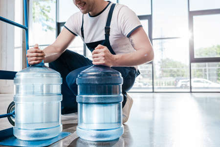 cropped view of happy delivery man holding blue bottles with water near hand truck