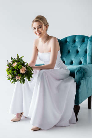 cheerful bride in elegant wedding dress holding flowers while sitting in armchair on white