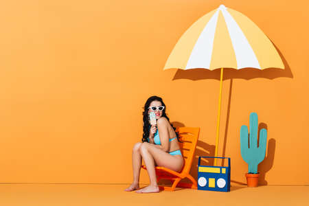 happy woman in sunglasses and swimsuit sitting on deck chair near boombox and umbrella while holding paper ice cream on orange Stok Fotoğraf