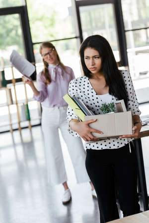selective focus of dismissed manager holding box with folders and documents near displeased boss