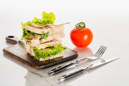 fresh green sandwiches on wooden cutting board near cutlery and tomato on white marble surface