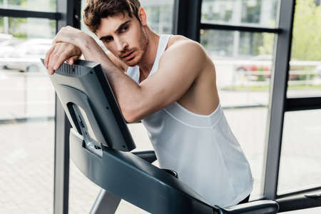 tired sportsman standing near treadmill in gym 스톡 콘텐츠