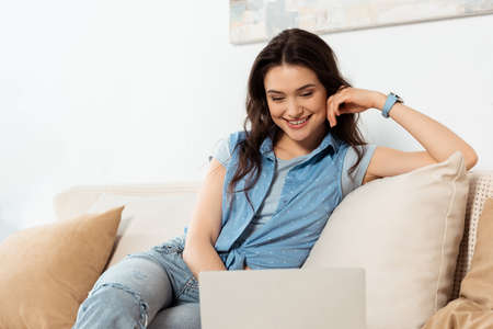 Selective focus of smiling girl using laptop on sofa 免版税图像