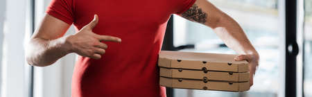 horizontal crop of delivery man pointing with finger at pizza boxes 免版税图像