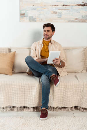 Handsome smiling man using digital tablet on couch at home
