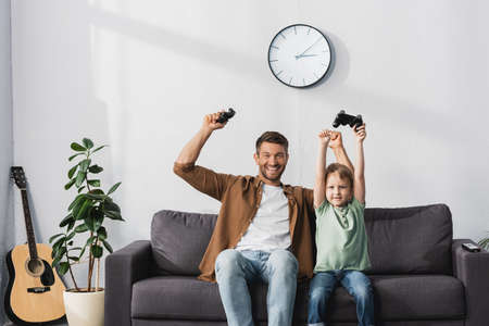 KYIV, UKRAINE - JUNE 9, 2020: happy father and son holding joysticks and showing winner gestures Фото со стока
