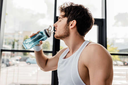 side view of sportsman with closed eyes drinking water and holding sports bottle