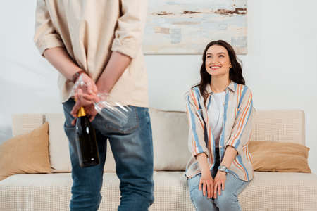 Selective focus of smiling girl looking at boyfriend hiding bottle of champagne and glasses at home 免版税图像