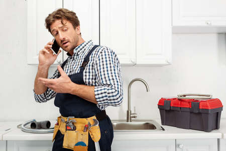 Plumber in tool belt talking on smartphone near pipes and toolbox on kitchen worktop