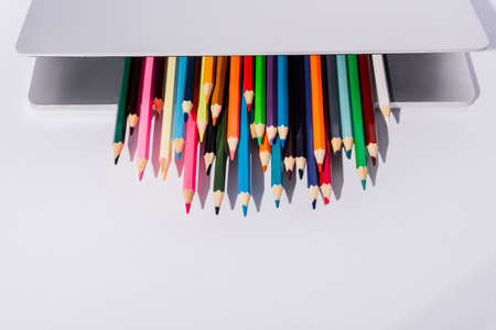 colored pencils in modern laptop on white background