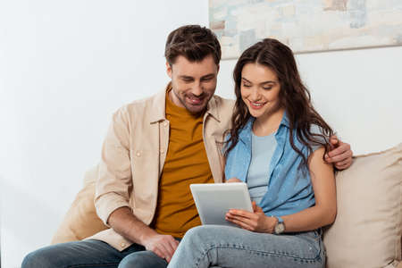 Handsome man embracing smiling girlfriend while using digital tablet at home Archivio Fotografico