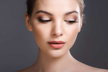 beautiful woman with makeup looking down isolated on grey