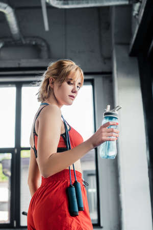 pretty sportswoman holding sports bottle with water in gym