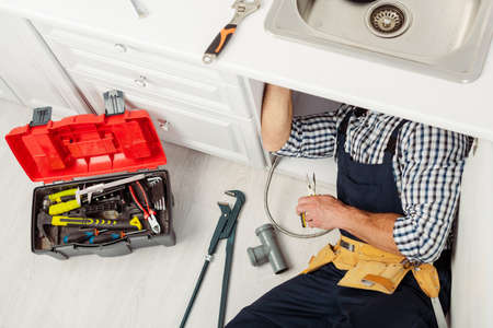 High angle view of plumber fixing kitchen sink with pliers near instruments and toolbox on floor Banco de Imagens