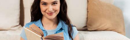 Panoramic shot of smiling woman looking at camera while reading book at home
