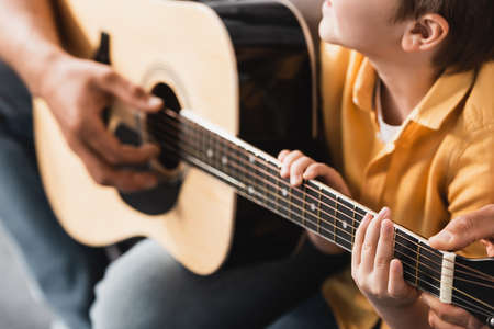 cropped view of father teaching son how to play acoustic guitar, selective focus
