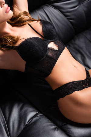Cropped view of sensual girl in bra and panties lying on black couch