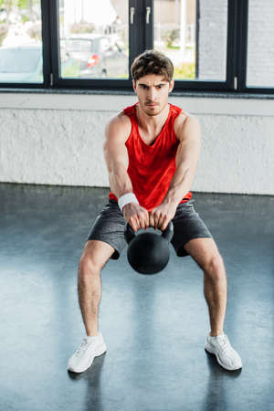 athletic man exercising with heavy dumbbell in sports center