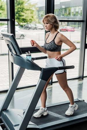 attractive sportswoman running on treadmill in gym 写真素材