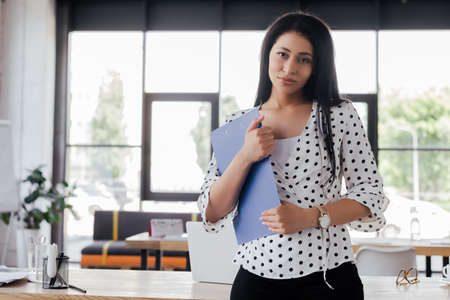 businesswoman holding clipboard while standing in office 스톡 콘텐츠