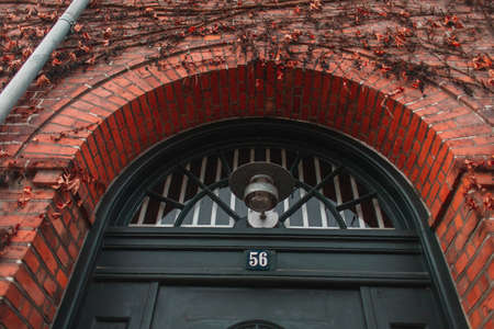 Low angle view of lantern near door and plant on brick facade of building in Copenhagen, Denmark