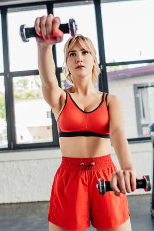 selective focus of athletic woman working out with dumbbells in sports center