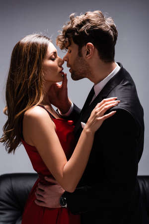 Side view of handsome man in suit touching lips of beautiful woman in red dress near couch on grey