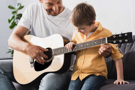 happy father teaching smiling son how to play acoustic guitar