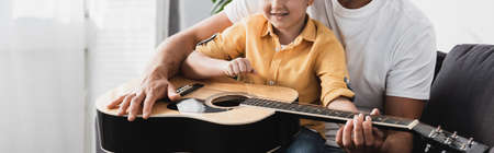 cropped view of boy sitting on fathers knees and learning how to play acoustic guitar Stock fotó