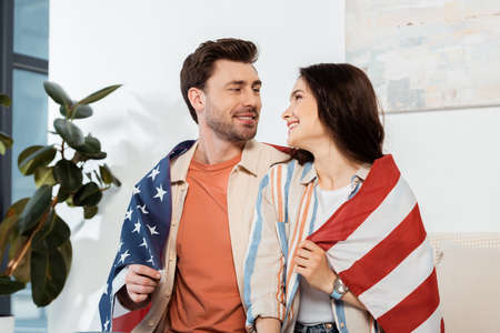 Smiling woman wrapped in american flag looking at boyfriend at home