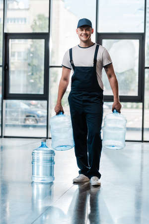 cheerful delivery man in uniform holding empty bottles near gallon of water