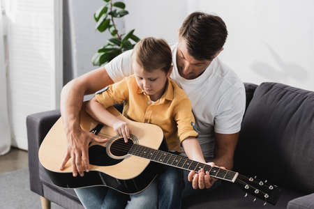 cute boy sitting of fathers knees and learning how to play acoustic guitar