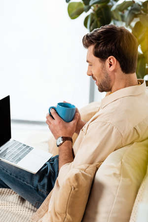 Side view of man holding coffee cup and looking at laptop on couch