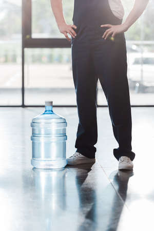 cropped view of delivery man in uniform standing with hands on hips near bottled water