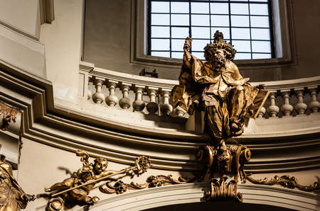 LVIV, UKRAINE - OCTOBER 23, 2019: gilded male statue near balcony with balustrade in dominican church