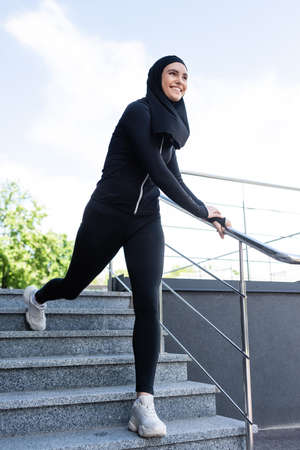 happy muslim sportswoman in hijab walking on stairs outside Banque d'images