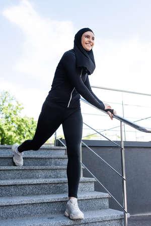 happy muslim sportswoman in hijab walking on stairs outside Imagens